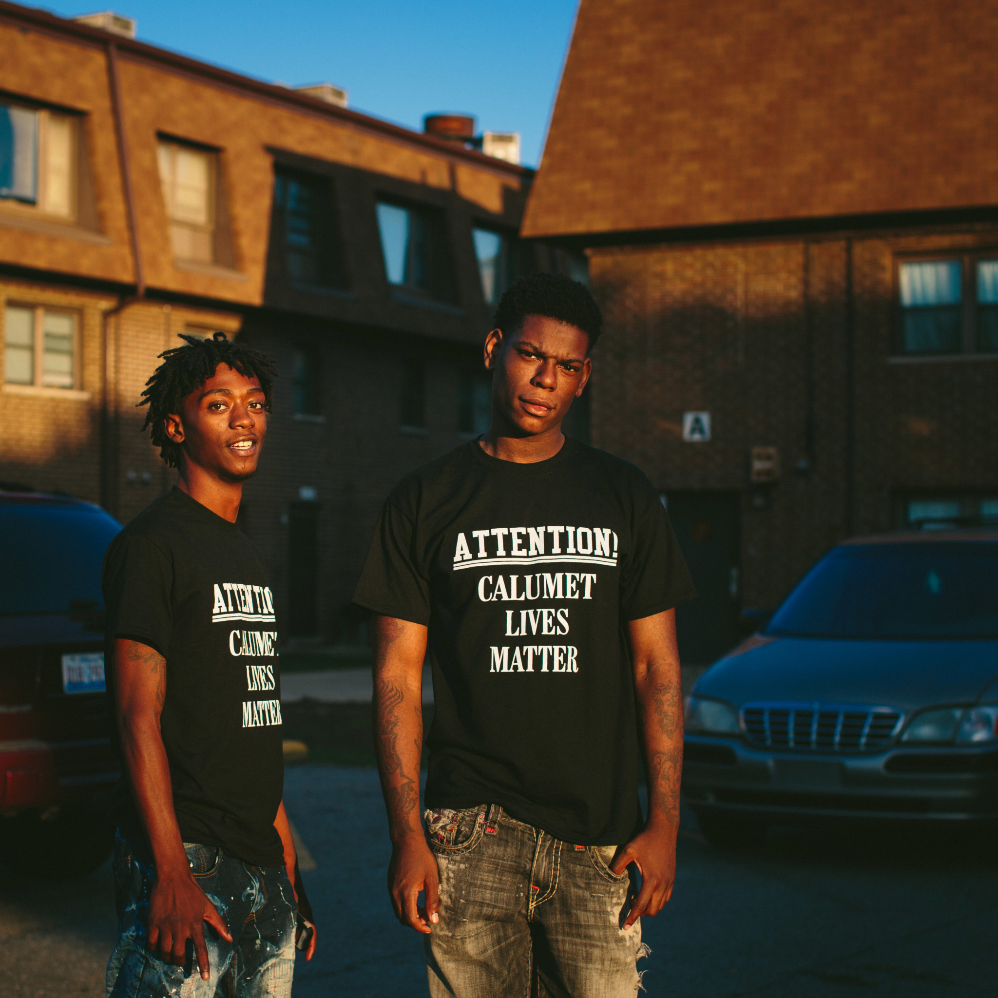 "18-year-old brothers Antwon Jones, at left, and D. Jones pose for a portrait near their home in the West Calumet Housing Complex. ""This is where we hang out every day. We are still here with the lead,"" D. Jones said."