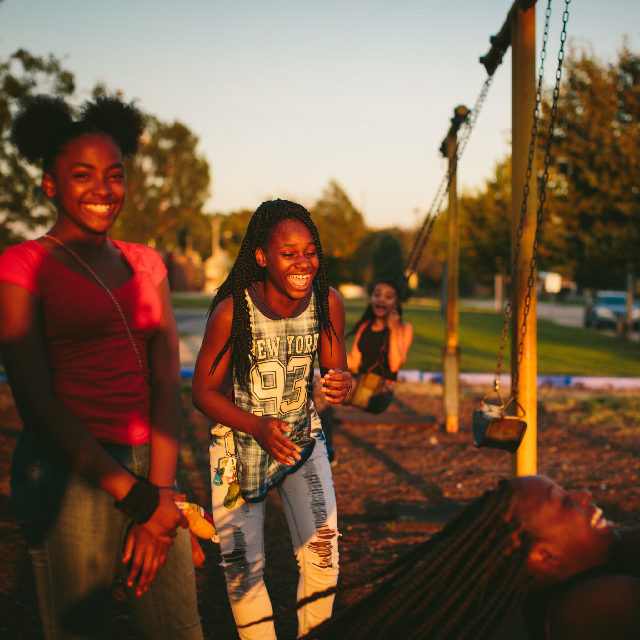 "From left, friends since childhood, Janae Peyton, 13, Ashanti France, 12, Irene Wooley, 13, and Tniyah Foxx, 12, swing at the park near the West Calumet Housing Complex in East Chicago, Indiana. The playground is part of the Carrie Gosch Elementary School, which has been turned into an EPA office. ""All my memories are here. I've got to move away from my friends,"" Peyton said."
