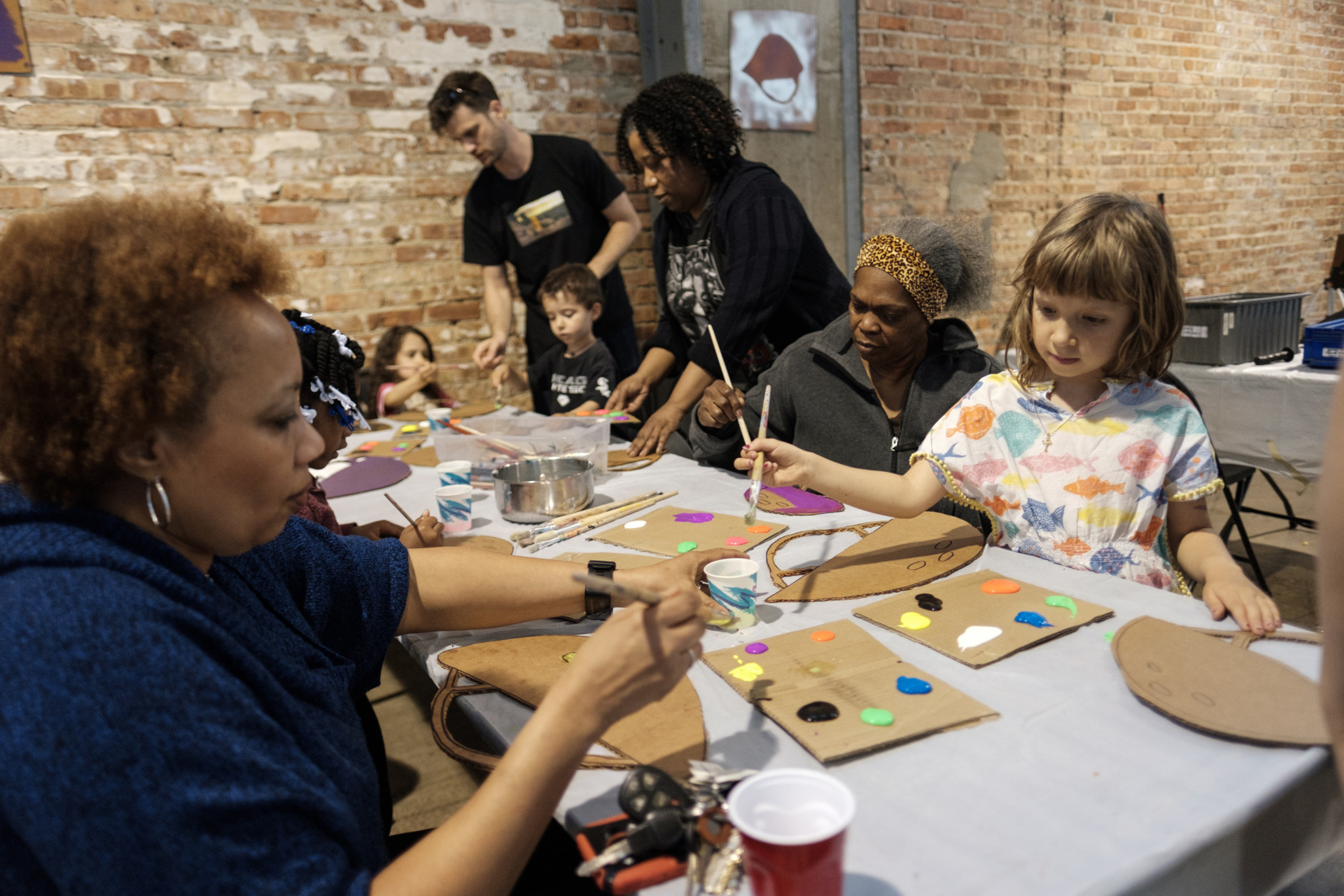 Guests painting cardboard bicycle helmets, one of several activities that took place after food and live performances (J. Michael Eugenio)