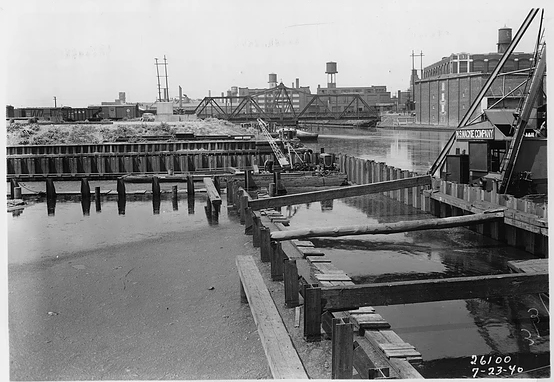 Looking west on July 23, 1940. The first step in construction of the Racine Avenue Pumping Station was constructing a sheet pile dock wall to close off the remaining part of the East Fork. A small channel was left to receive the discharge of stormwater. The station will be built on the vacant land west of the dock wall. The long-gone Iron Street bridge over the West Arm is in the background. (Metropolitan Water Reclamation District of Greater Chicago Archives)