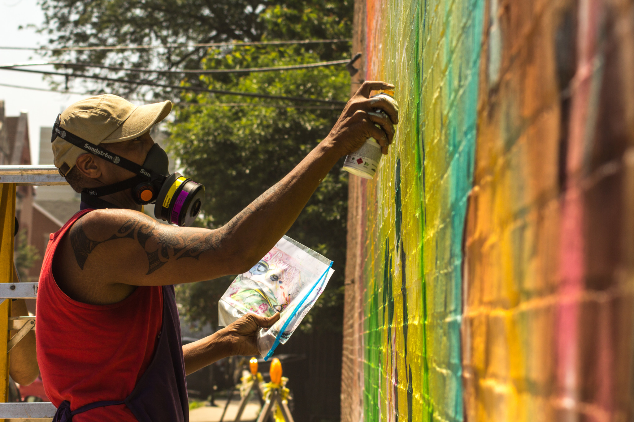 Lavie Raven painting his mural in Bronzeville (Rod Sawyer)