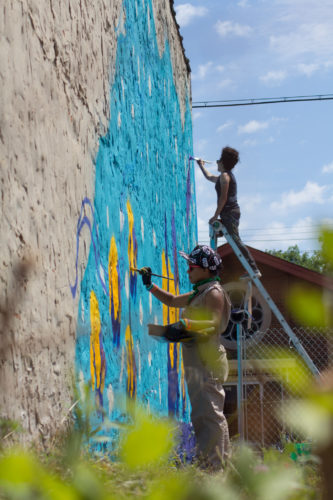 Sam Kirk and Jenny Q. work on their mural in West Englewood (Rod Sawyer)