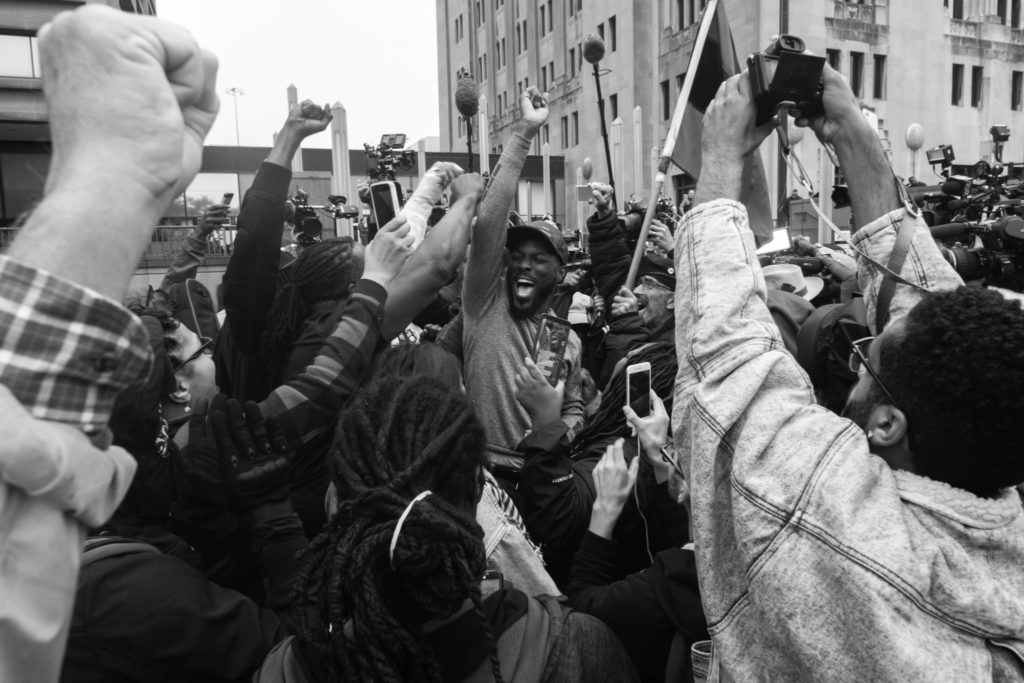 "Jedidiah Brown, middle, erupted in cheers with a crowd as they watch the broadcasted verdict for Jason Van Dyke outside Cook County. Jason Van Dyke, a white Chicago Police Officer, was convicted of Second Degree Murder and 16 counts of aggravated battery with a firearm for each of shots in the shooting death of 17-year-old Laquan McDonald. Soon after the conviction, Chicago activist took to the streets in protest for police reform, chanting, ""CPD! Guilty of conspiracy."""