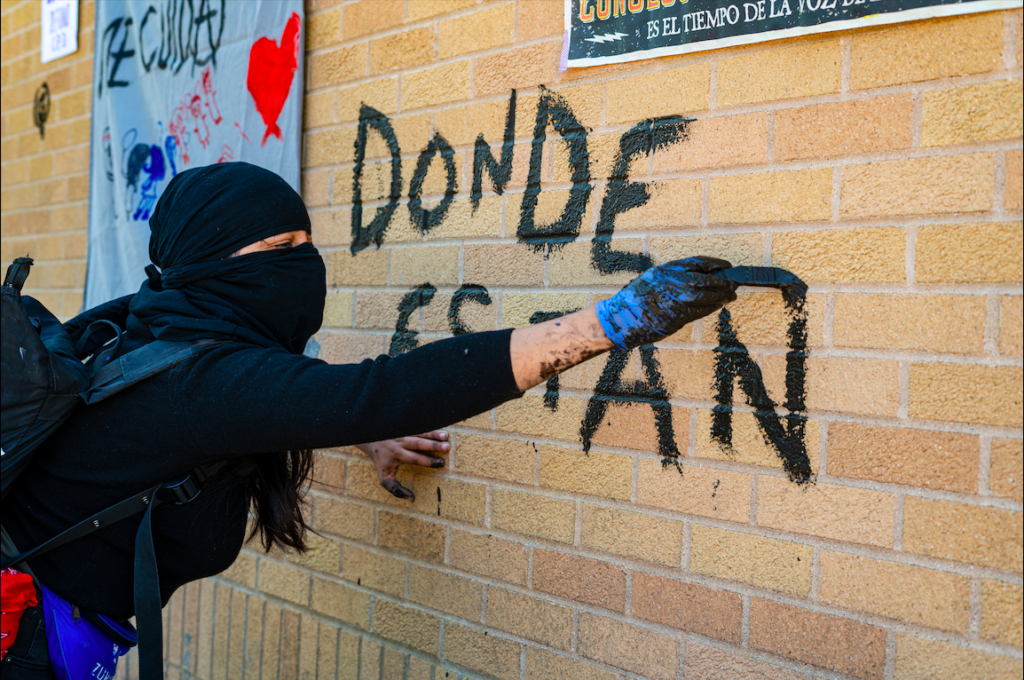 "An activist paints ""Donde estan / Where are they?"" in mud on the wall of the consulate. Photo by Óscar Sánchez."