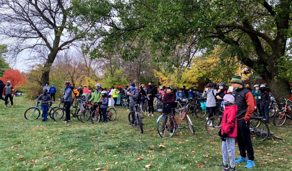About a hundred masked cyclists, adults and children, stand in a semi-circle in a park. Credit: Charmaine Runes