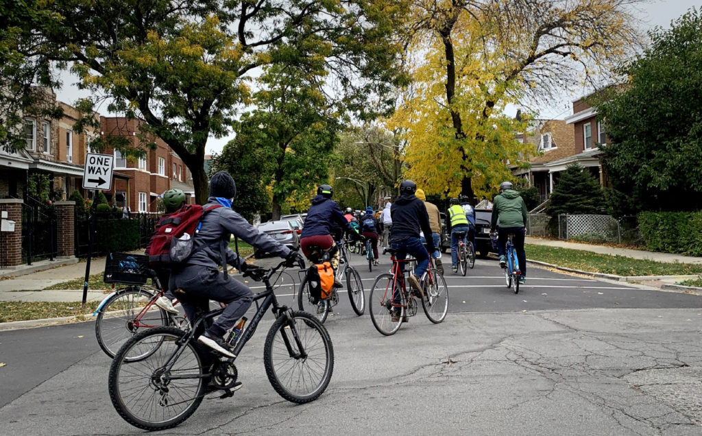 A large group of cyclists turns north onto tree-lined south Ridgeway Ave. Credit: Charmaine Runes