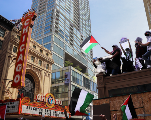 Some demonstrators scale an entrance to the 'L' to wave Palestinian flags above the group as they march on May 16, 2021 in Chicago. (Madison Muller/South Side Weekly)